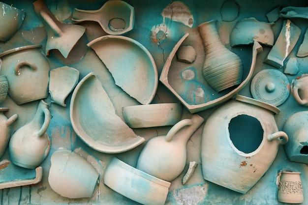 Een muur is versierd met servies van klei en geschilderd in een blauwe kleur
