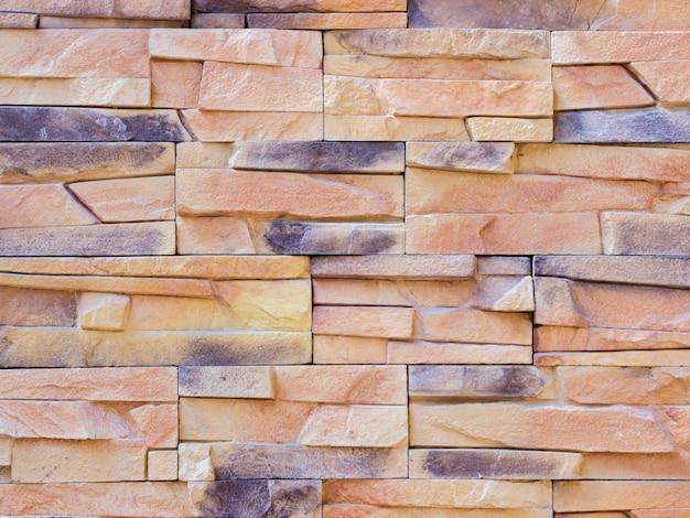Een muur van een kunstmatige beige en grijze stenen gevel met ruwe gebroken oppervlakken