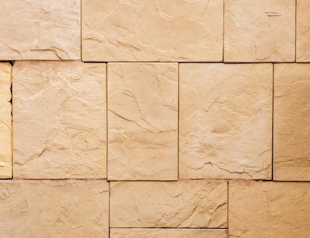 Een muur van een kunstmatige beige stenen gevel met ruwe gebroken oppervlakken