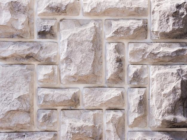 Een muur van een kunstmatige grijze stenen gevel met ruwe gebroken oppervlakken
