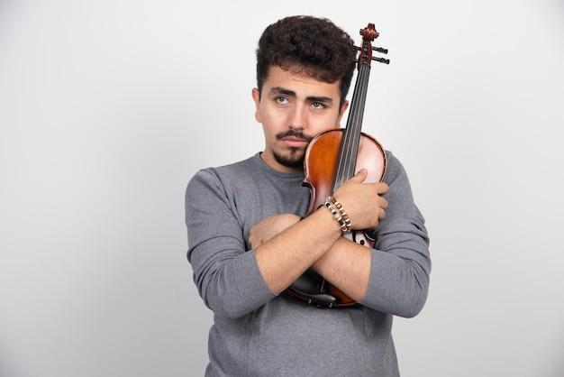 Een muzikant houdt zijn bruine houten viool vast en kijkt gestrest.