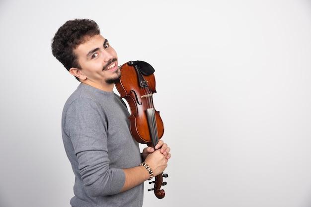 Een muzikant houdt zijn bruine houten viool vast en kijkt positief.