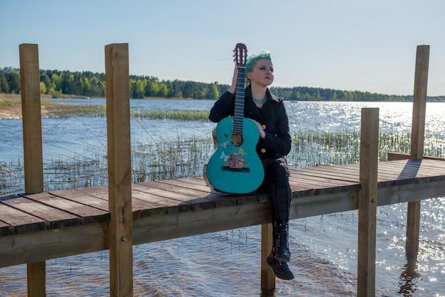 Een muzikant met blauw haar en een blauwe gitaar zit op een voetgangersbrug aan het meer en speelt muziek.