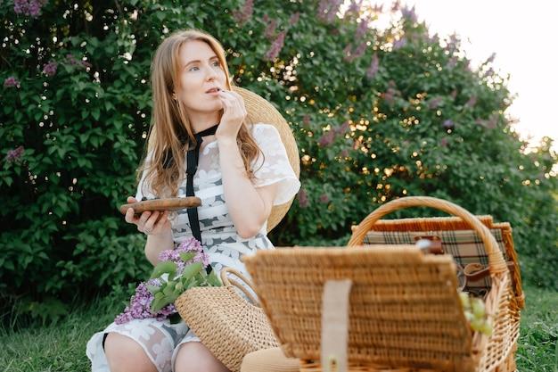 Een mysterieus roodharig meisje zit op een grasveld in een veld tegen de achtergrond van een groene jonge vrouw op een picknick eet verse, gezonde bosbessen
