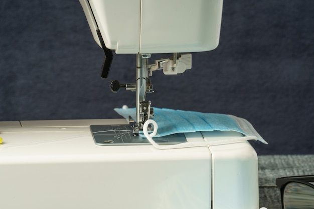 Een naaimachine naaide een medisch gezichtsmasker tijdens de gevaarlijke pandemie van het coronavirus