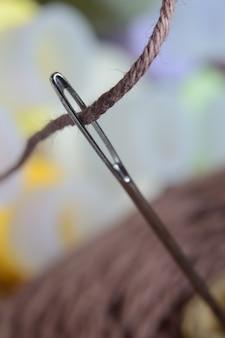 Een naainaald met bruine draad door het oog van de naald. macro.