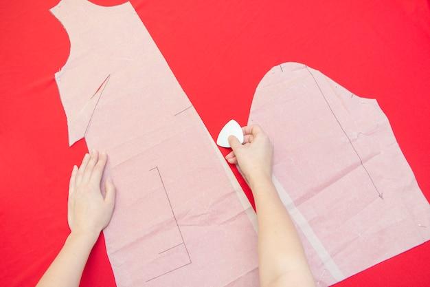 Een naaister omcirkelt een kledingstuk op een stof. kleding naaien. rode doek