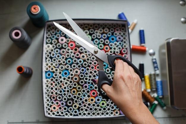 Een naaister trekt een schaar uit een doos met strengen gekleurde draden.