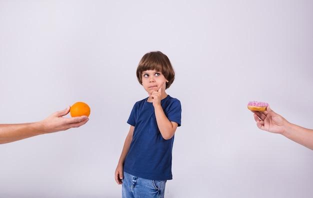 Een nadenkende kleine jongen in een t-shirt maakt een keuze tussen een sinaasappel en een donut op een witte achtergrond met een plek voor tekst