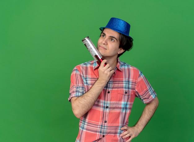 Een nadenkende, knappe blanke man met een blauwe feestmuts houdt een confettikanon vast en kijkt naar de zijkant