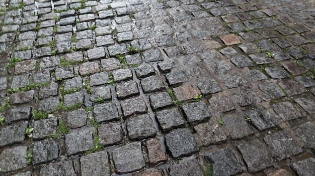 Een nat trottoir zorgt voor een glanzende achtergrond. mooie grijze stenen achtergrond. stenen weg, straatstenen in de oude stad tijdens de regen overdag.