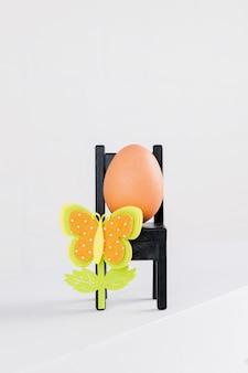 Een natuurlijk ei zit op zwarte stoel met pasen bloemdecoratie. minimale pasen concept idee.