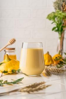 Een natuurlijke smoothie gemaakt van gele pompoen. herfstdrankje met honing en melk. op een lichte achtergrond, verticale positie