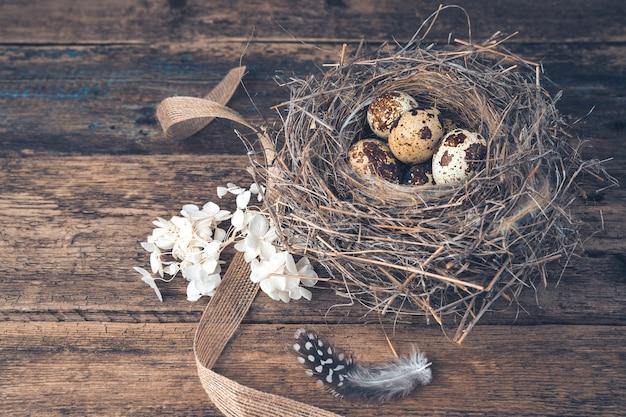 Een nest met kwarteleitjes, bloemen en veren op een houten achtergrond.