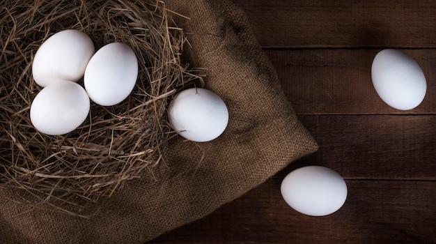 Een nest met witte eieren en eieren vallen uit het nest, bovenaanzicht.
