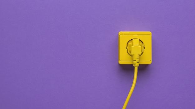 Een netsnoer aangesloten op een stopcontact op een paarse achtergrond. ruimte voor tekst.