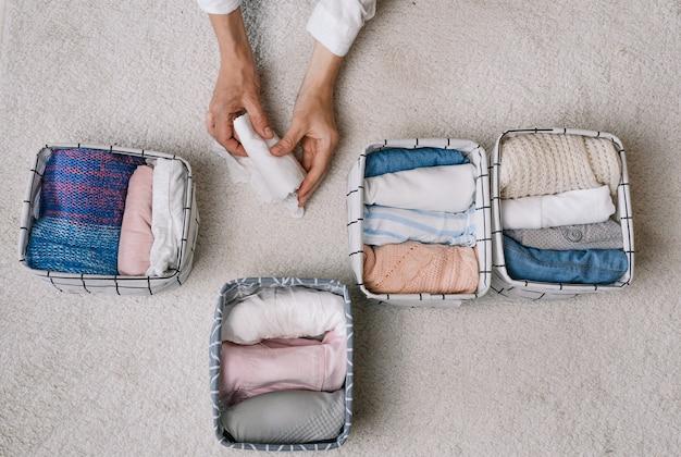 Een nette huisvrouw stopt tijdens de algemene schoonmaak dingen in een wascontainer met behulp van een modern opbergsysteem. bovenaanzicht het concept van een mooie en comfortabele organisatie