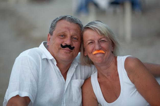 Een niet serieus portret. ouder paar poseren met nep snorren