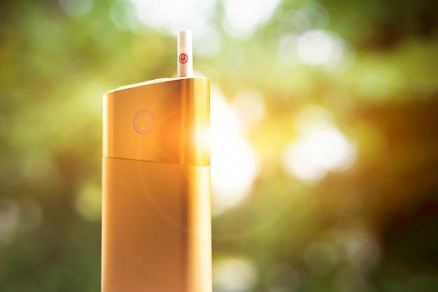 Een nieuw soort elektronische sigaret. iqos tabakverwarmingssysteem. mod voor roken staat met een sigaret. verwarmde sigaretten om te roken. veilige vorm van roken.
