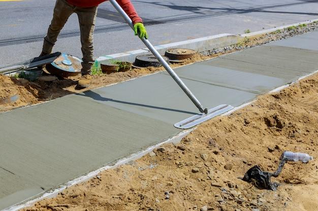 Een nieuw trottoir in nat beton neerleggen op vers gestorte trottoirs