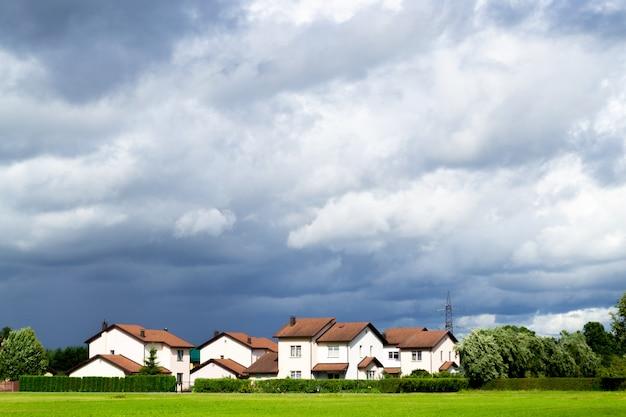 Een nieuwe cottage-nederzetting met een vlak groen gazon.