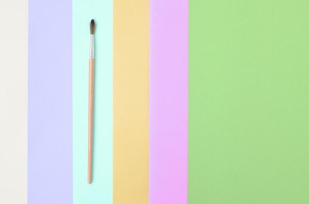 Een nieuwe kwast ligt op roze, blauw, groen, geel, violet en beige papier