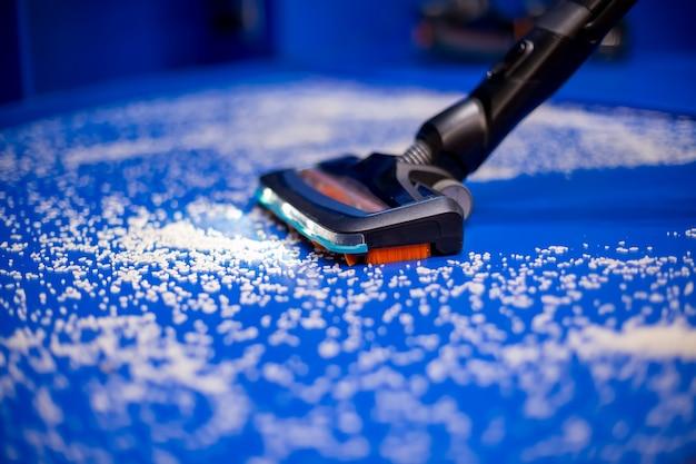 Een nieuwe stofzuiger met natte reiniging en leds reinigt de blauwe vloer van witte kruimels van dichtbij