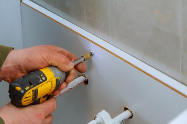 Een nieuwe timmerman voor badkamermeubels die een nieuw badkamermeubel installeert