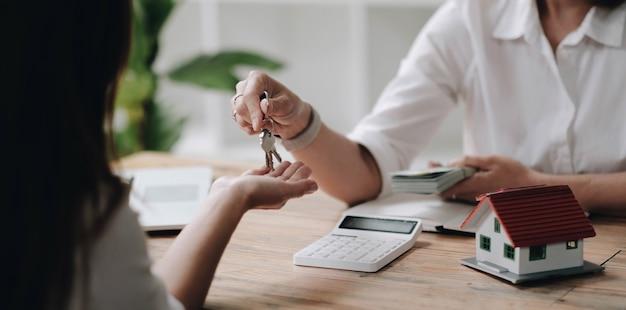 Een nieuwe verhuurder krijgt een huissleutelketting van een makelaar na het betalen van een huisborg. makelaar en cliënt, vastgoedinvestering.