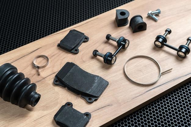 Een nieuwe verzameling auto-onderdelen lag plat op een donkere achtergrond, wijzig de details van de service