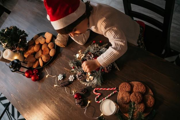 Een nieuwjaarskind zit aan een tafel in een rode nieuwjaarshoed en maakt met zijn eigen handen een kerstkrans