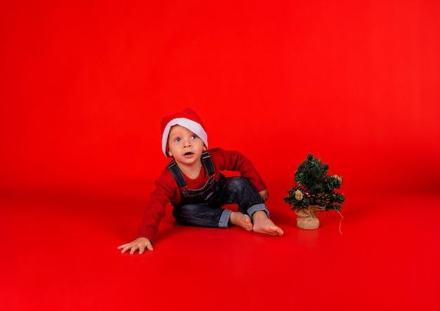 Een nieuwsgierige kleine jongen in een jumpsuit van denim en een kerstmuts
