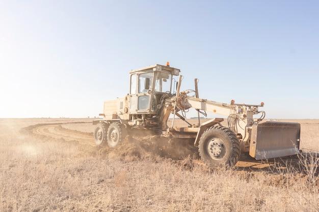 Een nivelleermachine die een nieuwe weg aan het maken is, graaf het grind in het veld