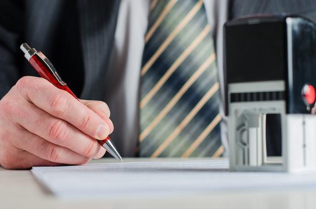 Een notaris of een advocaat ondertekent het document. een vulpen in de hand van een man.