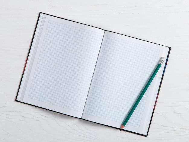 Een notebook en een potlood op een witte tafel, een plek voor tekst, kopie ruimte.