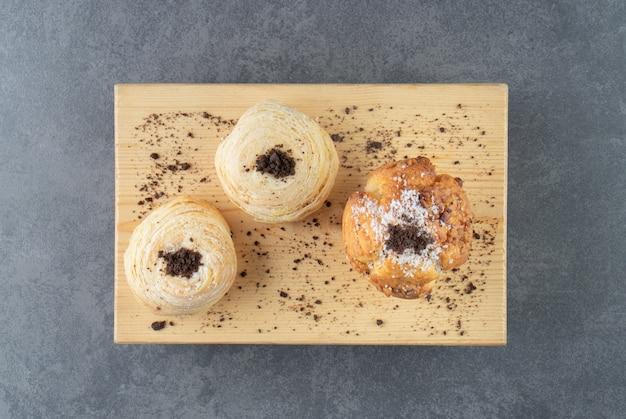 Een notenmuffin met gebak en cacaopoeder op een houten bord