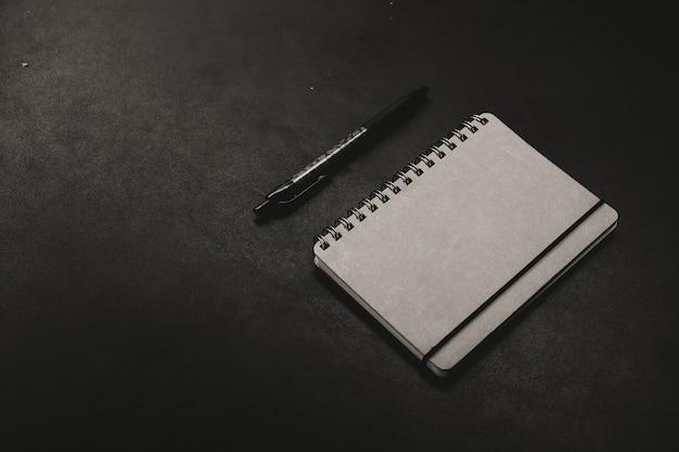 Een notitieblok met een pen op een donkere achtergrond