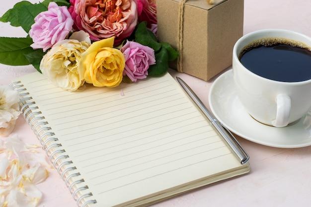 Een notitieboek met bruine rozen en een kopje koffie op tafel