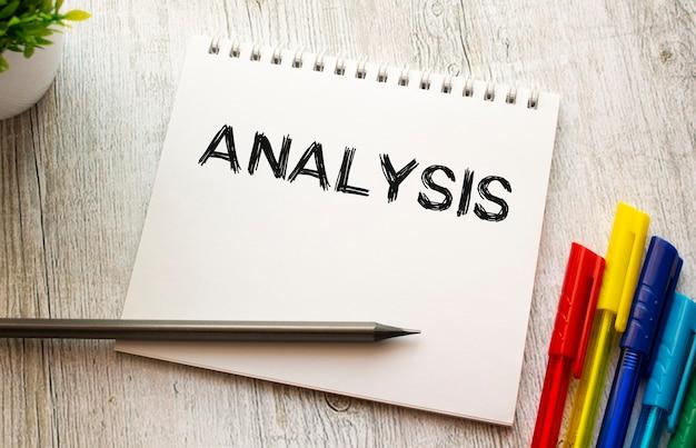 Een notitieboekje met de tekst analysis op een wit vel ligt op een houten tafel met gekleurde pennen.