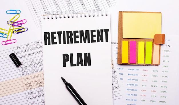 Een notitieboekje met de woorden pensioenplan, een stift, gekleurde paperclips en helder notitiepapier liggen op het oppervlak van de grafieken