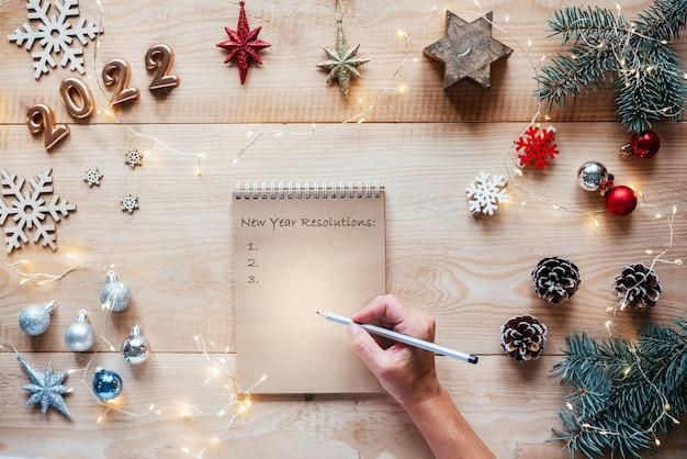 Een notitieboekje met nieuwjaarsresoluties op kerstachtergrond