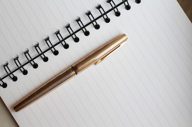 Een notitieboekje met schone bladen, een envelop en een gouden pen op de tafel