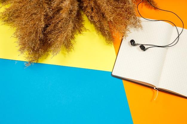 Een notitieboekje met schone witte vellen voor opname met een pen op een gekleurde achtergrond, een telefoon en koptelefoon, verfrommelde droge takken in de buurt. opnemen, rapporteren, bericht, brief. plaats voor tekst