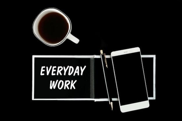 Een notitieboekje met zwarte pagina's, smartphone en een kopje koffie op een zwarte achtergrond. de inscriptie dagelijks werk op het kladblok.