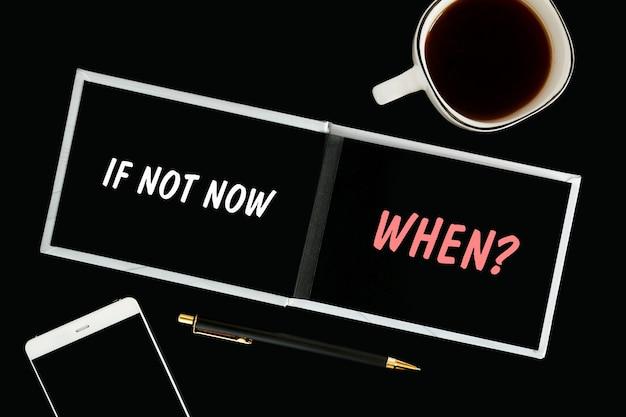 Een notitieboekje met zwarte pagina's, smartphone en een kopje koffie op een zwarte achtergrond. het opschrift if not now when op het kladblok.