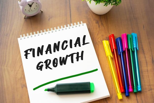 Een notitieboekje op een veer met de tekst financile groei ligt op een bruin houten tafel.
