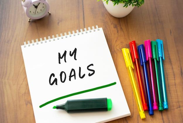 Een notitieboekje op een veer met de tekst my goals op een wit vel ligt op een bruin houten tafel met gekleurde pennen. bedrijfsconcept.