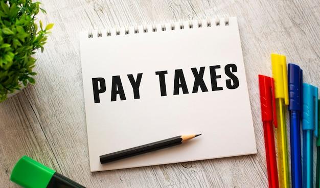 Een notitieboekje op een veer met de tekst pay taxes op een wit vel ligt op een houten tafel met gekleurde pennen. bedrijfsconcept.