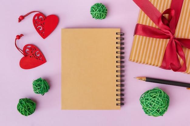 Een notitieboekje voor een groetinscriptie, een geschenk en hartjes op een roze tafel. valentijnsdag