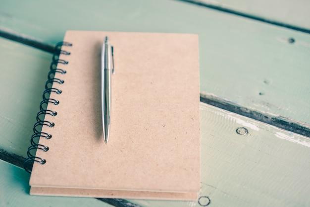 Een notitieboekjedocument met een pen op houten lijst, onderwijs, bedrijfsstillevenconcept